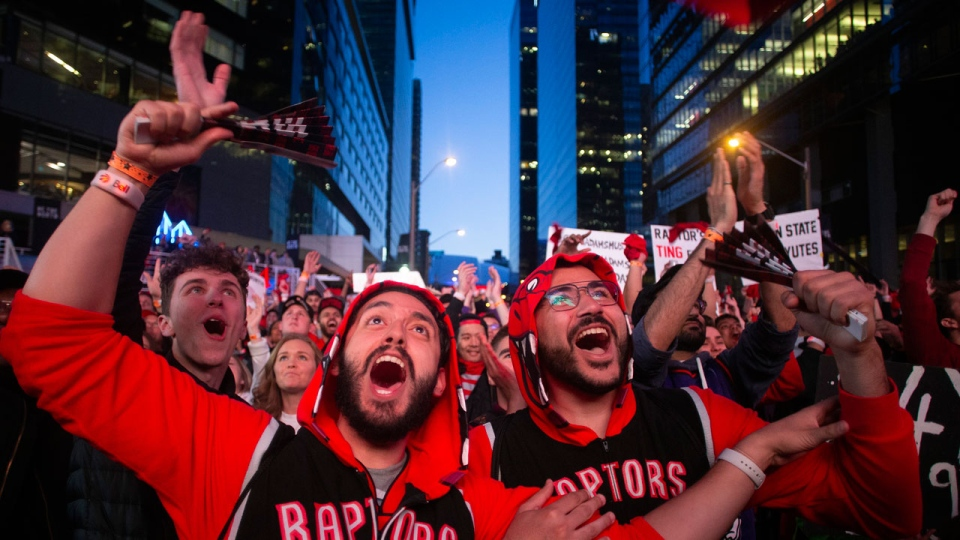 """Toronto Raptors fans watch Game 2 of the NBA Finals between the Raptors and the Golden State Warriors the in the fan area known as """"Jurassic Park"""" outside Scotiabank Arena in Toronto on Sunday, June 2, 2019. THE CANADIAN PRESS/Chris Young"""