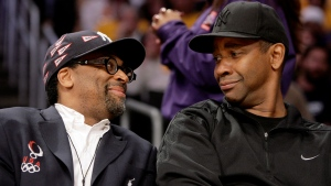 FILE - In this May 19, 2009 file photo, director Spike Lee, left, and Denzel Washington talk during the first half of Game 1 of the NBA basketball Western Conference finals between the Los Angeles Lakers and the Denver Nuggets in Los Angeles. Lee will honor Washington's illustrious career by presenting his friend and collaborator the American Film Institute's Life Achievement Award. AFI says Tuesday, June 4, 2019, that Lee will present the actor and director with the honor at a gala Thursday, June 6 at the Dolby Theatre in Hollywood. (AP Photo/Mark Avery, File)