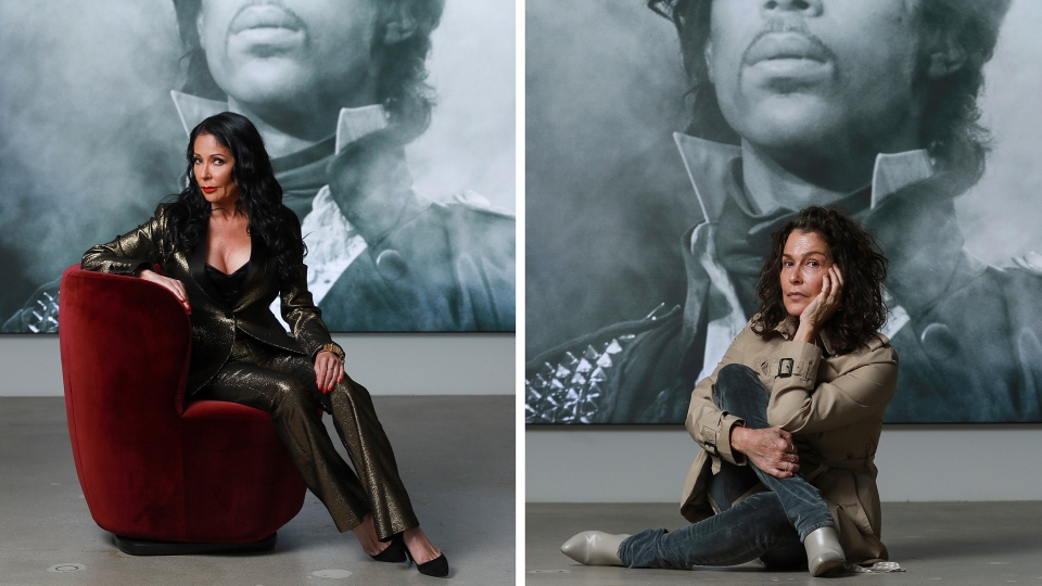 "In this photo combination, singers Apollonia Kotero, left, and Susannah Melvoin pose in front of a photo of Prince at Warner Music Group in Los Angeles on Friday, May 31, 2019. Kotero and Melvoin are among several artists who spoke with The Associated Press about their experience working with Prince in advance of the release of his posthumous album, ""Originals,"" due out this month. (Photo by Mark Von Holden/Invision/AP)"