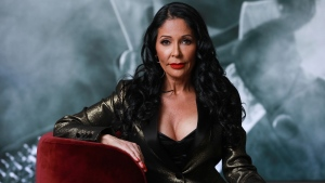 Apollonia Kotero poses for a portrait in front of a photo of Prince at Warner Music Group in Los Angeles on Friday, May 31, 2019. (Photo by Mark Von Holden/Invision/AP)