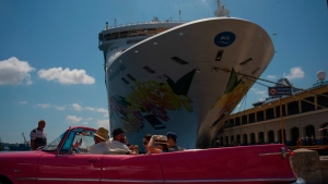 Tourists who have just disembarked from a cruise liner, tour the city aboard a vintage American convertible, in Havana, Cuba, Tuesday, June 4, 2019. The Trump administration has imposed major new travel restrictions on visits to Cuba by U.S. citizens, banning stops by cruise ships and ending a heavily used form of educational travel as it seeks to further isolate the communist government. (AP Photo/Ramon Espinosa)