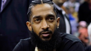 This March 29, 2018 file photo shows rapper Nipsey Hussle at an NBA basketball game between the Golden State Warriors and the Milwaukee Bucks in Oakland, Calif. (AP Photo/Marcio Jose Sanchez, File)