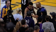 Toronto Raptors guard Kyle Lowry, middle, gestures next to referee Marc Davis (8) near the front row of fans during the second half of Game 3 of basketball's NBA Finals between the Golden State Warriors and the Raptors in Oakland, Calif., Wednesday, June 5, 2019. A fan seated courtside for Game 3 of the NBA Finals was ejected after shoving Lowry when the Raptors star crashed into a row of seats while trying to save a ball from going out of bounds on Wednesday night. (AP Photo/Tony Avelar)