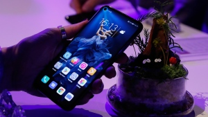 In this Tuesday, May 21, 2019 file photo, a member of the media tries out new Huawei Honor 20 series of phones following their global launch in London. (AP Photo/Alastair Grant, file)