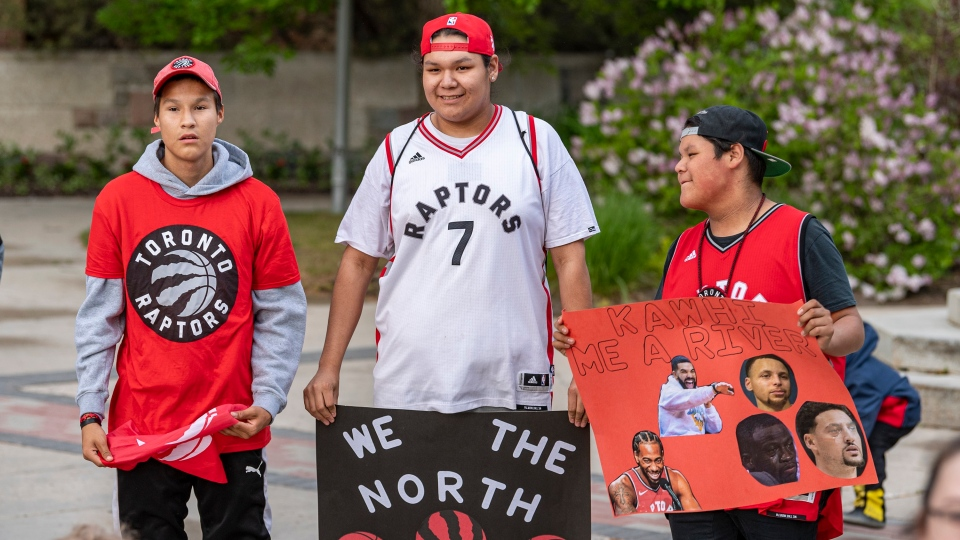 Joreil Bear, left to right, Jalen Severight-Benson, and Darren Severight hold signs a watch during the NBA finals game 5 viewing party at city hall's civic centre in Saskatoon, Monday, June 10, 2019. THE CANADIAN PRESS/Liam Richards