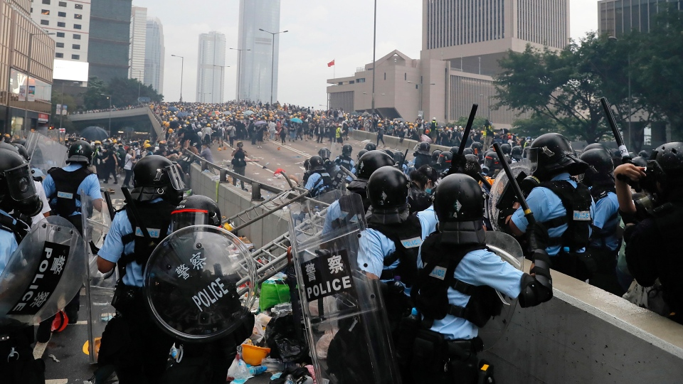 Riot police gather face off with demonstrators near the Legislative Council in Hong Kong, Wednesday, June 12, 2019. Hong Kong police fired tear gas and high-pressure water hoses against protesters who had massed outside government headquarters Wednesday in opposition to a proposed extradition bill that has become a lightning rod for concerns over greater Chinese control and erosion of civil liberties in the semiautonomous territory. (AP Photo/Kin Cheung)