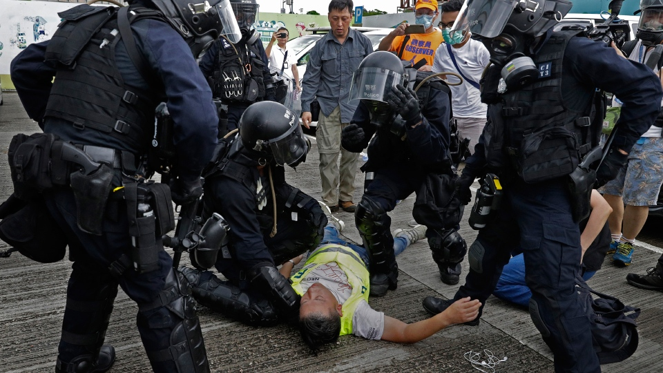 A cameraman lies injured after riot police fire tear gas on protesters outside the Legislative Council in Hong Kong, Wednesday, June 12, 2019. (AP Photo/Vincent Yu)
