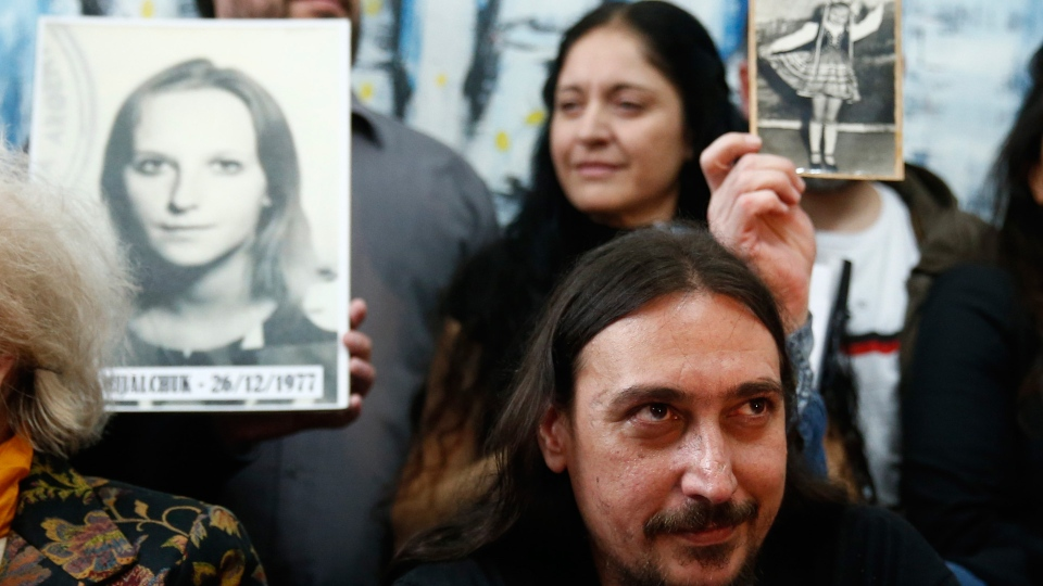 Javier Matias Darroux Mijalchuk sits in front of pictures of his biological mother Elena Mijalchuk, during a news conference in Buenos Aires, Argentina, Thursday, June 13, 2019. The Grandmothers of the Plaza de Mayo say DNA tests have determined the identity of Javier Matías Darroux Mijalchuk, taken from his mother as a baby by the country's former dictatorship. This brings the number of such cases to 130. (AP Photo/Marcos Brindicci)
