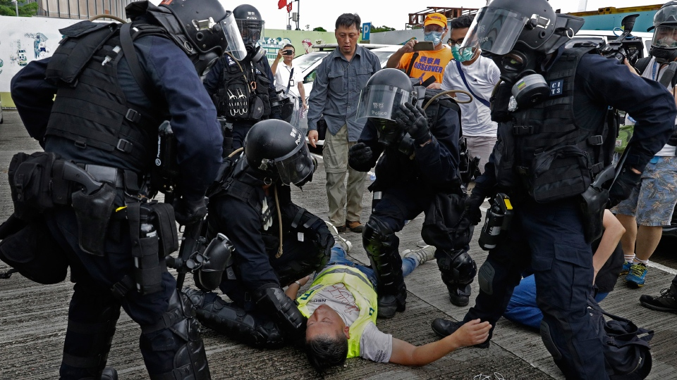 In this file photo taken Wednesday, June 12, 2019, a cameraman lies injured after riot police fire tear gas on protesters outside the Legislative Council in Hong Kong. Hong Kong police have resorted to harsher-than-usual tactics to suppress protesters this week in the city's most violent turmoil in decades. Police fired rubber bullets and beanbag rounds at the crowds, weapons that have not been widely used in recent history. (AP Photo/Vincent Yu, File)