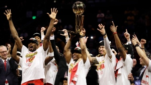Toronto Raptors center Serge Ibaka, left, guard Kyle Lowry, center, and guard Danny Green, third from right, celebrate with teammates after the Raptors defeated the Golden State Warriors in Game 6 of basketball's NBA Finals in Oakland, Calif., Thursday, June 13, 2019. (AP Photo/Ben Margot)