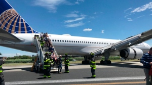 This photo provided by Caroline Craddock shows emergency personnel help passengers off a plane after a  United Airlines plane skidded off the runway after landing at Newark Liberty International Airport on Saturday, June 15, 2019 in Newark, N.J.  (Caroline Craddock via AP)