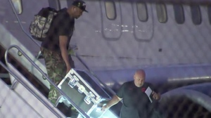 Staffers holding what is believed to be the Larry O'Brien trophy disembark at Pearson International Airport on June 15. (CP24)