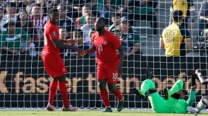 Canada forwards Junior Hoilett (10) celebrates with Jonathan David, left, after scoring on Martinique goalkeeper Loïc Chauvet during the second half of a CONCACAF Gold Cup soccer match in Pasadena, Calif., Saturday, June 15, 2019. Canada won 4-0. (AP Photo/Ringo H.W. Chiu)