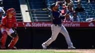 Seattle Mariners' Edwin Encarnacion, right, hits a two-run home run as Los Angeles Angels catcher Jonathan Lucroy watches during the seventh inning of a baseball game Sunday, June 9, 2019, in Anaheim, Calif. (AP Photo/Mark J. Terrill)