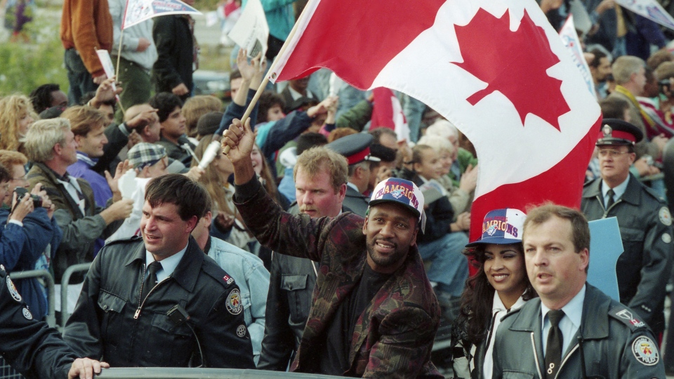 Toronto Blue Jays' Joe Carter waves the Canadian flag alongside his wife Diana during a World Series victory parade in Toronto on Sunday, October 24, 1993. The Raptors' historic NBA championship win last week marked the first time a Canadian team has won one of the big four professional sports championships since the Toronto Blue Jays won the 1993 World Series. THE CANADIAN PRESS/Frank Gunn