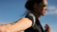A woman who is the mother of a victim in the 2016 La Loche shooting, shows her tattoo in support of her son who was shot in the arm, in Saskatoon, Wednesday, June, 12, 2019. THE CANADIAN PRESS/Kayle Neis