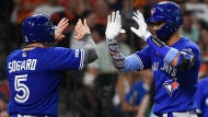 Toronto Blue Jays' Lourdes Gurriel Jr., right, celebrates his two-run home run off Houston Astros starting pitcher Brad Peacock with Eric Sogard during the fifth inning of a baseball game, Sunday, June 16, 2019, in Houston. (AP Photo/Eric Christian Smith)