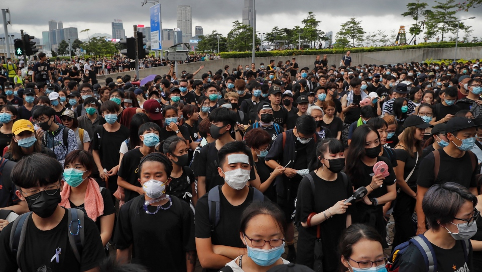 Protesters wearing masks gather near the Legislative Council as they continuing protest against the unpopular extradition bill in Hong Kong, Monday, June 17, 2019. A member of Hong Kong's Executive Council says the city's leader plans to apologiz