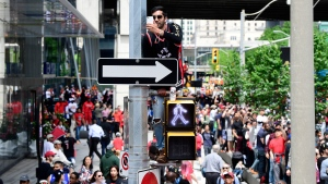 A fan takes a photo standing on a crosswalk light on a street light pole during the 2019 Toronto Raptors Championship parade in Toronto on Monday, June 17, 2019. THE CANADIAN PRESS/Frank Gunn