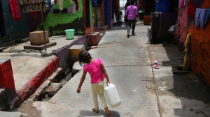 A girl walks carrying drinking water at a slum in Mumbai, India, Wednesday, June 19, 2019. India is facing a 43% deficiency on monsoon rains across the country by its late arrival by a week in June, according to India Meteorological Department. Temperatures last week soared to 48 degrees (118 degrees Fahrenheit) in northern and western India, creating heatwave conditions. (AP Photo/Rafiq Maqbool)