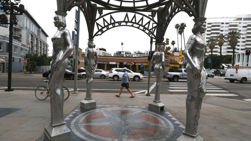 """A pedestrian walks past the """"Four Ladies of Hollywood"""" gazebo on Hollywood Boulevard in Los Angeles, on Wednesday June 19, 2019. Officials say someone climbed the more than two-story tall public art piece and stole a statue of Marilyn Monroe. Los Angeles Councilman Mitch O'Farrell says a witness saw someone climb the gazebo on the Hollywood Walk Fame and sawed off the statue. (AP Photo/Richard Vogel)"""