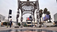 "A pedestrian walks past the ""Four Ladies of Hollywood"" gazebo on Hollywood Boulevard in Los Angeles, on Wednesday June 19, 2019. Officials say someone climbed the more than two-story tall public art piece and stole a statue of Marilyn Monroe. Los Angeles Councilman Mitch O'Farrell says a witness saw someone climb the gazebo on the Hollywood Walk Fame and sawed off the statue. (AP Photo/Richard Vogel)"