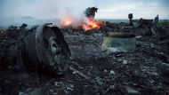 In this Thursday, July 17, 2014 file photo, a man walks amongst the debris at the crash site of a passenger plane near the village of Hrabove, Ukraine. An international team of investigators building a criminal case against those responsible in the downing of Malaysia Airlines Flight 17 is set to announce progress in the probe on Wednesday June 19, 2019, nearly five years after the plane was blown out of the sky above conflict-torn eastern Ukraine. (AP Photo/Dmitry Lovetsky, File)