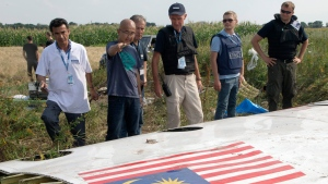 FILE In this file photo taken on Wednesday, July 23, 2014, Malaysian investigators along with members of the OSCE mission in Ukraine, examine a piece of the crashed Malaysia Airlines Flight 17 in the village of Petropavlivka, Donetsk region, eastern Ukraine. International investigators on Wednesday, June 19, 2019 announced murder charges against three Russians, including a prominent separatist rebel commander, and one Ukrainian, for their alleged roles in blowing a Malaysia Airlines passenger jet out of the sky five years ago, a shocking attack that killed all 298 people on board. (AP Photo/Dmitry Lovetsky, File)