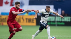 "Vancouver Whitecaps' Lucas Venuto, right, runs with the ball as Toronto FC's Drew Moor attempts to stop him during the first half of an MLS soccer game in Vancouver on May 31, 2019. It's a role he has held in the past with the Colorado Rapids, but it was a special night for Toronto FC veteran Drew Moor when he donned the captain's armband in their last game on June 7.""I always love wearing the armband,"" Moore said following a training session earlier in the week. ""I'll never turn it away, that's for sure."" THE CANADIAN PRESS/Darryl Dyck"