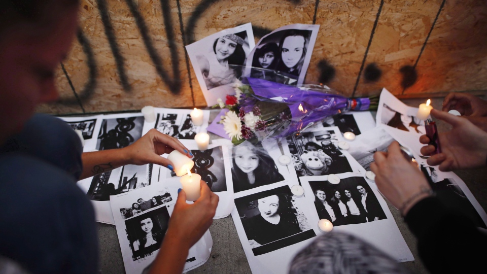 People light candles and leave photos of 18-year-old victim Reese Fallon at a memorial remembering the victims of a shooting on Sunday evening on Danforth Ave., in Toronto on Monday, July 23, 2018. THE CANADIAN PRESS/Mark Blinch