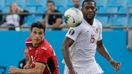Canada's Doneil Henry (15) and Cuba's Luis Paradela (23) chase the ball during the first half of a CONCACAF Golf Cup soccer match in Charlotte, N.C., Sunday, June 23, 2019. (AP Photo/Chuck Burton)
