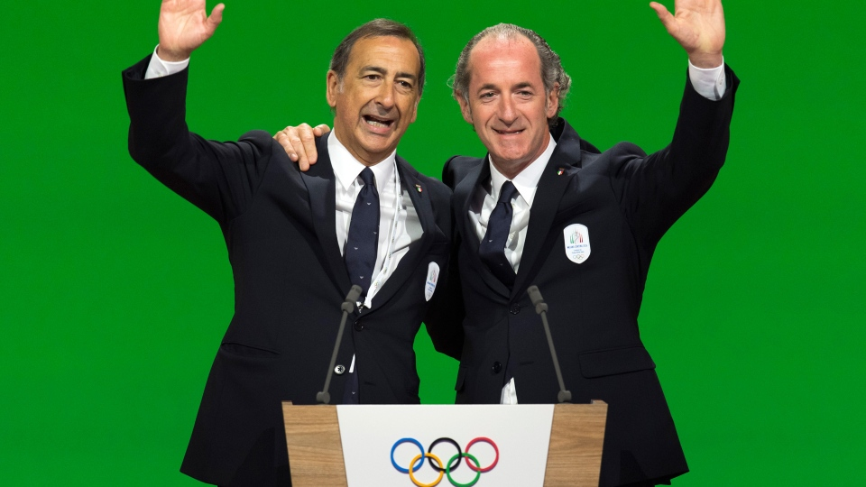 From left, Mayor of Milan Giuseppe Sala and Italy's Veneto Region President Luca Zaia wave during the presentation final presentation of the Milan-Cortina candidate cities the first day of the 134th Session of the International Olympic Committee (IOC), at the SwissTech Convention Centre, in Lausanne, Switzerland, Monday, June 24, 2019. The host city of the 2026 Olympic Winter Games will be decided during the134th IOC Session. Stockholm-Are in Sweden and Milan-Cortina in Italy are the two candidate cities for the Olympic Winter Games 2026. (Laurent Gillieron/Keystone via AP)