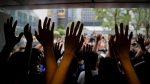 Protesters gesture inside the Hong Kong Revenue Tower as they block the building lobby to prevent people from entering in Hong Kong, Monday, June 24, 2019. Mass protests in recent weeks have occurred in Hong Kong over legislation that was seen as increasing Beijing's control and over police treatment of the protesters. (AP Photo/Kin Cheung)