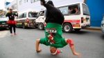 In this Dec. 12, 2018 photo, Venezuelan Karin Rojas balances on her head as she breakdances with Angel Fernandez for tips from commuters in Lima, Peru. (AP Photo/Cesar Olmos)