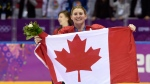 In this Feb. 21, 2014, file photo, Canada's Hayley Wickenheiser celebrates with the Canadian flag after beating the USA 3-2 in overtime at the Sochi Winter Olympics in Sochi, Russia. Wickenheiser is the Toronto Maple Leafs new assistant director of player development. (AP Photo/Paul Chiasson, The Canadian Press, File)