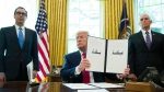 FILE - In this Monday, June 24, 2019 file photo, President Donald Trump holds up a signed executive order to increase sanctions on Iran, accompanied by Treasury Secretary Steve Mnuchin, left, and Vice President Mike Pence, in the Oval Office of the White House, in Washington. A year after President Trump's unilateral withdrawal from the 2015 deal, the U.S. and Iran are already locked in a volatile standoff. (AP Photo/Alex Brandon, File)