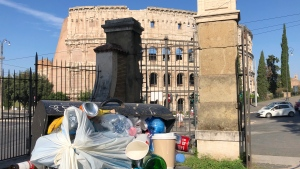 In this photo taken on Tuesday, June 25, 2019, a man walks past a pile of garbage as St. Peter's Dome is visible in background, in Rome. Doctors in Rome are warning of possible health hazards caused by overflowing trash bins in the city streets, as the Italian capital struggles with a renewed garbage emergency aggravated by the summer heat. (AP Photo/Andrew Medichini)
