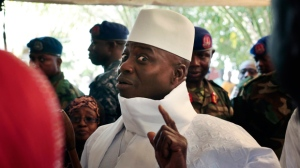 In this Thursday, Dec. 1, 2016 file photo, Gambia's President Yahya Jammeh shows his inked finger before voting in Banjul, Gambia. Gambia's ex-President Yahya Jammeh looted the tiny West African nation of $1 billion through fear and privilege during his 22 years in power, an amount more than 10 times higher than originally estimated by the new government, leaving the country in lingering debt, according to a report on Wednesday March 27, 2019, by the investigative group Organized Crime and Corruption Reporting Project. (AP Photo/Jerome Delay, File)