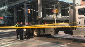 Investigators stand at the scene of a fatal crash on Queen Street East and Victoria Street on June 26, 2019. (Cristina Tenaglia/CP24)