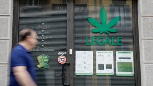 "In this Thursday, June 6, 2019 photo a man walks by the entrance of a cannabis light store, in which writing reads ""Legal"" on the shop window, in Milan, Italy, Thursday, June 6, 2019. It's been called Italy's ''Green Gold Rush,'' a flourishing business around light marijuana that has created 15,000 jobs and an estimated 150 million euros worth of annual revenues in under three years. But the budding sector is facing a political and judicial buzzkill. (AP Photo/Luca Bruno)"