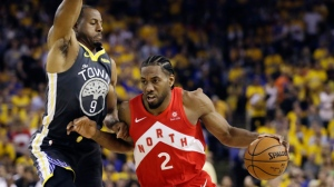 In this June 13, 2019, file photo, Toronto Raptors forward Kawhi Leonard (2) drives against Golden State Warriors forward Andre Iguodala (9) during the first half of Game 6 of basketball's NBA Finals in Oakland, Calif. A person familiar with the negotiations says the Los Angeles Clippers will be landing Kawhi Leonard as a free agent after they acquire Paul George from the Oklahoma City Thunder in a massive trade for players and draft picks. (AP Photo/Ben Margot, File)