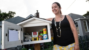 Melissa Rafael poses next to a free food pantry she erected on her property to help ease food insecurity in her neighbourhood, in Toronto, on Friday, July 5, 2019. THE CANADIAN PRESS/Christopher Katsarov