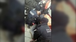 A screengrab from viewer video posted online shows multiple Toronto police officers and a TTC fare inspector pinning a teenage boy to the ground on the 512 St. Clair streetcar route. (Facebook / Bethany EJ McBride)