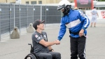 Canadian race car driver Robert Wickens greets a fan ahead of the first of two practice sessions at the Honda Indy in Toronto, on Friday, July 12, 2019. THE CANADIAN PRESS/Andrew Lahodynskyj
