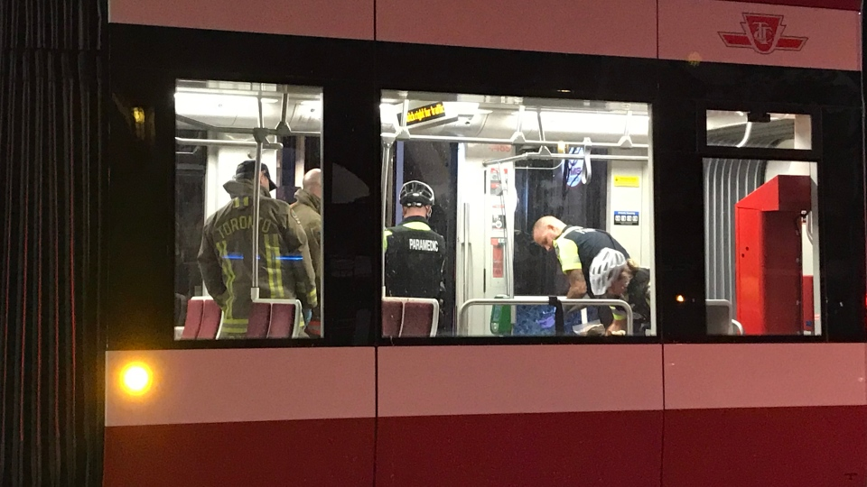 Emergency workers are shown on the 501 Queen streetcar following a stabbing call late Sunday night. (Kelly Linehan)
