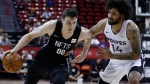 Brooklyn Nets' Rodions Kurucs drives around Minnesota Timberwolves' Jordan Murphy Jr. during the first half of an NBA summer league basketball game Sunday, July 14, 2019, in Las Vegas. (AP Photo/John Locher)