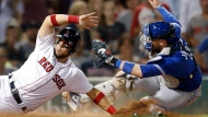 Toronto Blue Jays' Danny Jansen, right, tags out Boston Red Sox's Michael Chavis at home plate during the sixth inning of a baseball game in Boston, Monday, July 15, 2019. (AP Photo/Michael Dwyer)