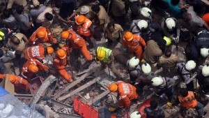 Rescuers work at the site of a building that collapsed in Mumbai, India, Tuesday, July 16, 2019. A four-story residential building collapsed Tuesday in a crowded neighborhood in Mumbai, India's financial and entertainment capital, and several people were feared trapped in the rubble, an official said. (AP Photo/Rajanish Kakade)