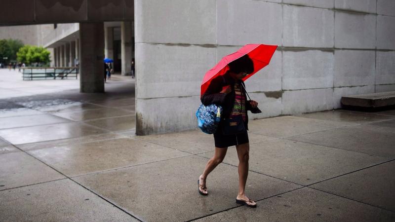People with umbrellas walk through city hall in Toronto. THE CANADIAN PRESS/Christopher Katsarov