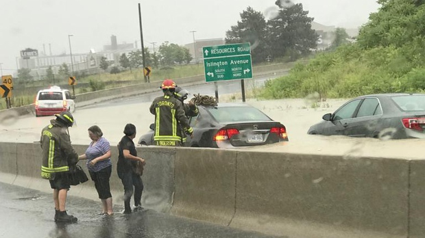 Firefighters help motorists get out of their flooded vehicle at Highway 401 and Islington on July 17, 2019. (@SairaSMirza/Twitter)